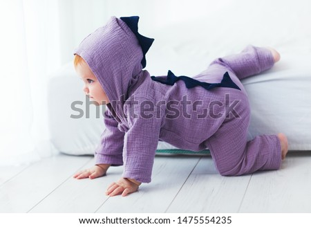 beautiful smiling, nine month old, infant baby girl in dinosaur costume, is sitting on the bed