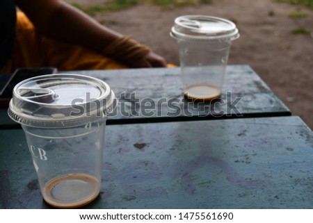 Toronto, Ontario: August 7, 2019: Two plastic cups on a park bench at Trinity Bellwoods Park between friends. #1475561690