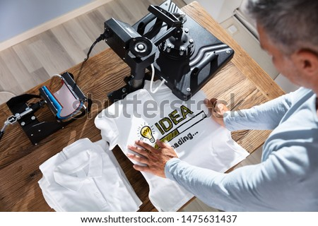 Man Printing Image On T-Shirt In Workshop Royalty-Free Stock Photo #1475631437