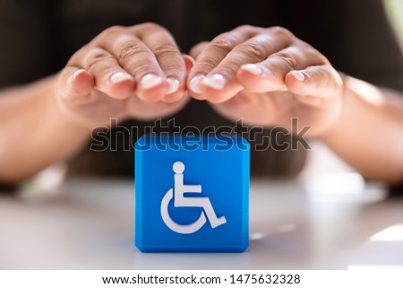 Close-up Of A Person's Hand Protecting Blue Cubic Block With Disabled Icon #1475632328