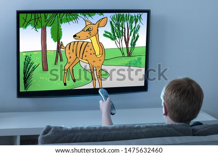 Rear View Of Boy Sitting On Sofa Watching Cartoon On Television