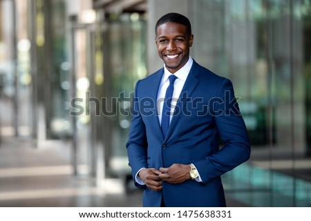 Handsome charming cheerful african american businessman in swanky modern stylish suit and tie, colorful, classy, office building #1475638331