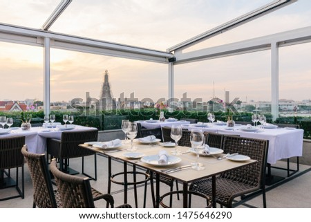 BANGKOK, THAILAND. NOV 22, 2016: Renovated Wat Arun (The Temple of Dawn) with boats moving over Chaophraya river that view from restaurant with dining tables in the evening in Bangkok, Thailand. #1475646290