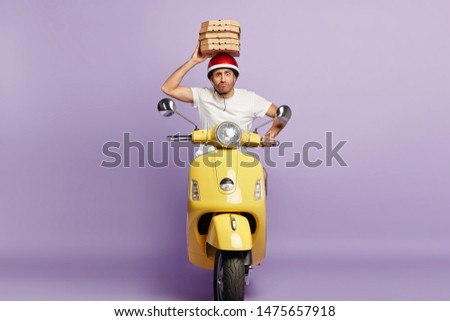Food delivery service. Busy male courier hurries as conveys cardboard boxes with pizza, tries bring order in time, drives scooter, holds containers over head, wears protective helmet, white t shirt #1475657918