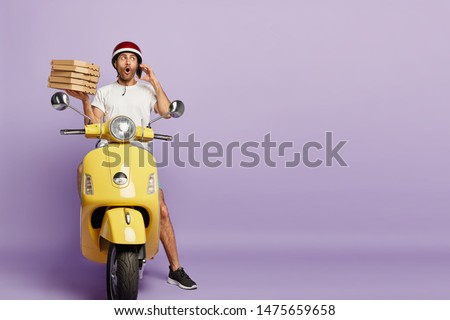 Surprised busy male delivers pizza, receives order from customer over smartphone, asks about address carries pile of cardboard containers, sits on motorbike, conveys food items isolated on purple wall #1475659658