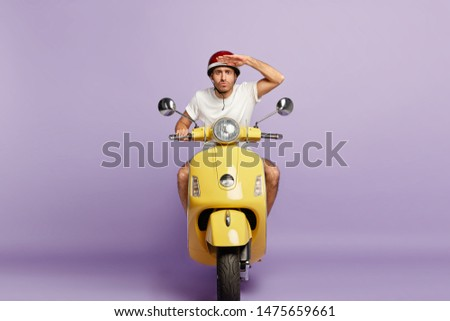 Serious motorbike driver keeps palm near forehead, concentrated into distance, being attentive on road, wears protective headgear, being excellent motorcyclist, isolated on purple background #1475659661