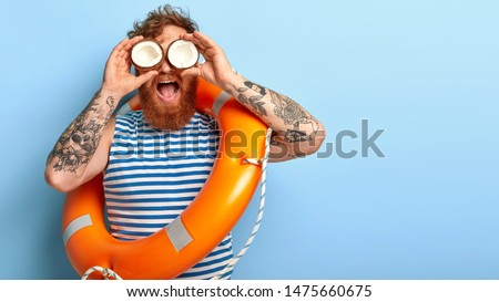 Funny redhead holiday maker wears sailor vest, poses with inflated lifebuoy, ready to give help for people at sea, holds coconuts on eyes, pretends looking in binocular notices something into distance #1475660675
