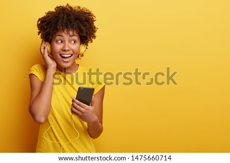 Photo of female meloman listens favourite playlist in headphones, enjoys good sound, holds cellular with multimedia application, wears bright casual clothing, isolated on yellow background. Monochrome #1475660714