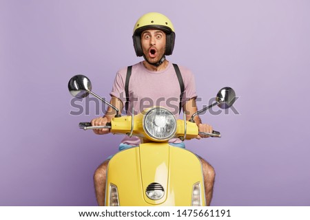Astonished professional motorcyclist travels on fast transport, shocked with horrible accident on road, drives yellow scooter, wears headgear and purple t shirt. People, driving, reaction, stupor. #1475661191