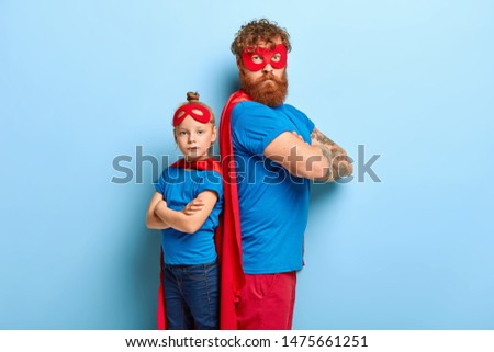 Self confident father and daughter stand back to each other, keep arms folded, look seriously at camera, wear special superhero costumes, play game, isolated on blue background. Ginger family #1475661251