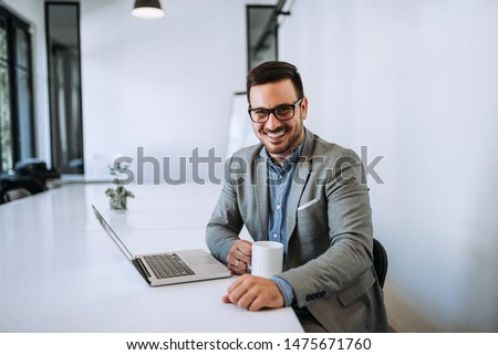 Businessman holding cup of coffee in office. #1475671760