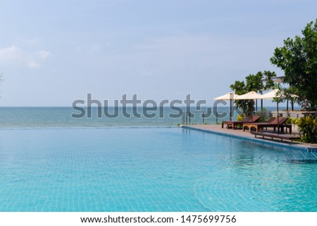 Large swimming pool with sun light effected around with long wooden chairs and large umbrella and background sea. #1475699756