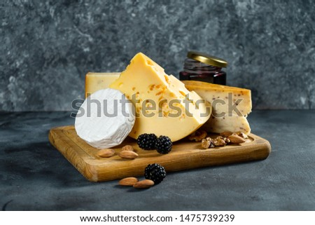 Cheese Assortment on a dark stone background with copy space. Different types: Camembert, cheese with spices, Dutch cheese on wooden cutting board. almond, blackberries and jam with cheese. Soft focus #1475739239