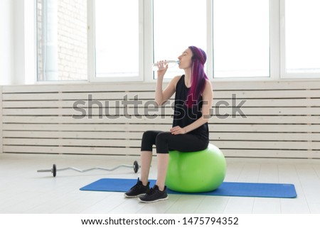 Charming slim young girl hipster with colored hair drinks water while sitting on a fitball next to a barbell near the window In the bright gym. Concept of regular fitness classes. #1475794352