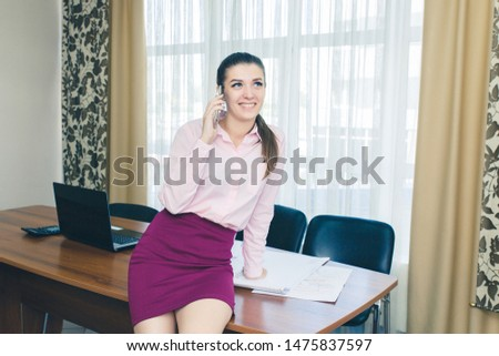 Business woman in the workplace talks on the phone. Smiling girl with phone. #1475837597