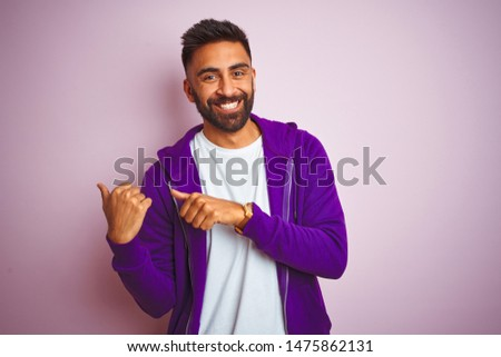 Young indian man wearing purple sweatshirt standing over isolated pink background Pointing to the back behind with hand and thumbs up, smiling confident #1475862131
