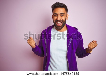 Young indian man wearing purple sweatshirt standing over isolated pink background celebrating surprised and amazed for success with arms raised and open eyes. Winner concept. #1475862155