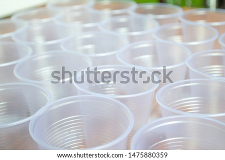 transparent disposable plastic cups on wooden table #1475880359