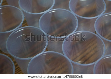 transparent disposable plastic cups on wooden table #1475880368