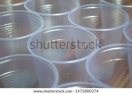 transparent disposable plastic cups on wooden table #1475880374