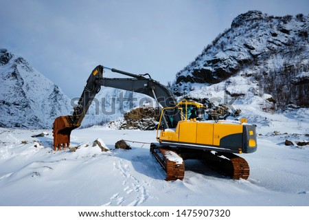 Old excavator with excavator bucket in winter. Road construction in snow. Lofoten islands, Norway #1475907320