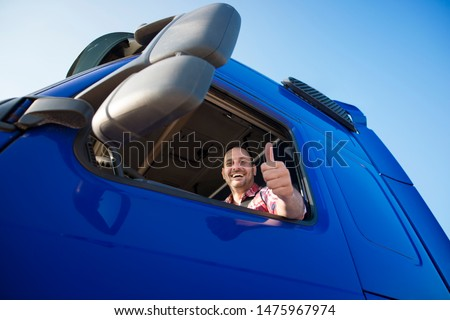 Truck driver sitting in his truck showing thumbs up. Trucker occupation. transportation services. #1475967974