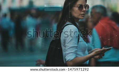 Facial recognition and search and surveillance of a person in the modern digital age, the concept. Young woman with phone in crowd of people on the street, identification and modern technology #1475971292
