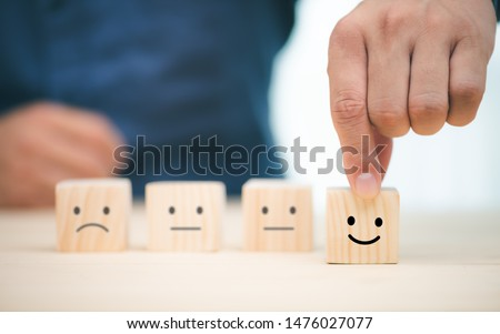Hand of a businessman chooses a smiley face on wood block cube, The best excellent business services rating customer experience, Satisfaction survey concept #1476027077