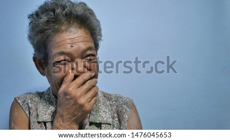 The Asian women's laughing. She has white and short hair. The picture concepts are happy, family, relaxing with the copy space.