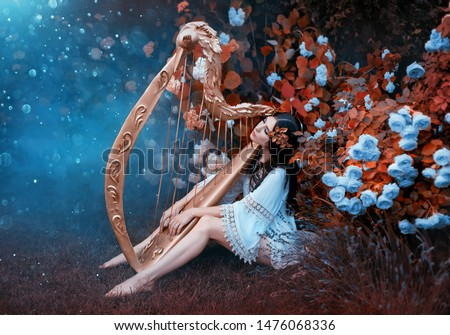 Woman in a vintage short dress with bare legs. A goddess with a gold laurel wreath sits in the garden near blooming roses and hydrangeas with a harp. Light and blessing pours on the girl from heaven #1476068336