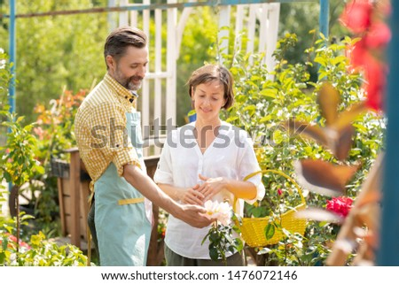 Contemporary gardener showing woman new sorts of white flowers growing in pots #1476072146