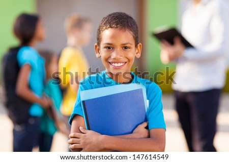 cheerful african male elementary school student holding text books #147614549