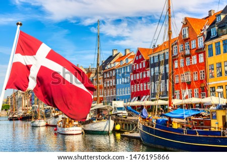 Copenhagen iconic view. Famous old Nyhavn port in the center of Copenhagen, Denmark during summer sunny day with Denmark flag on the foreground. #1476195866