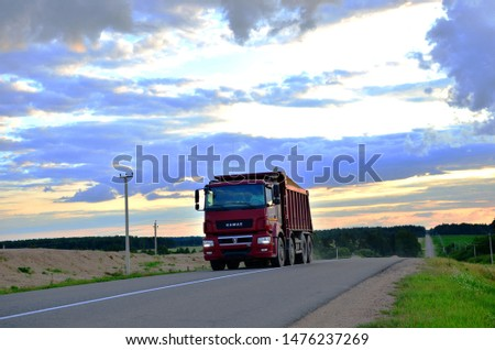 Minsk, Belarus 16.07.2019:  KAMAZ - 65801-001-68 (T5) dump truck (8x4)transports sand along the highway against the backdrop of sunset and beautiful countryside landscape #1476237269
