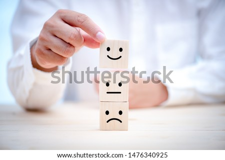 Hand of a businessman chooses a smiley face on wood block cube, The best excellent business services rating customer experience, Satisfaction survey concept #1476340925