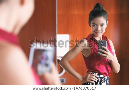 Mirror selfie confident Asian woman feeling pretty good in her body self-esteem taking photo with mobile phone in home closet looking at her slim weight loss waistline.