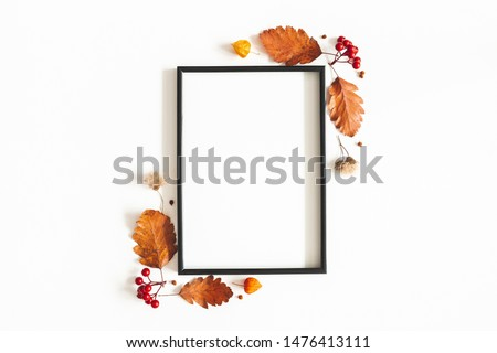 Autumn composition. Photo frame, flowers, leaves on white background. Autumn, fall, thanksgiving day concept. Flat lay, top view, copy space #1476413111