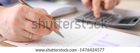 Accountant Calculate Finance Company Expenses. Man Accounting Financial Data Using Calculator, Graph, Stationery at Workplace. Secretary Analyzes Economy Revenue. Payment Growth Calculation #1476424577