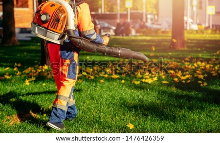 Male worker removes leaf blower leaves lawn of garden Autumn. #1476426359