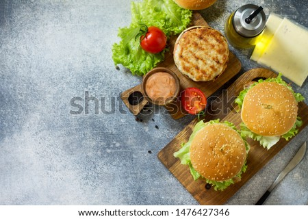 Delicious grilled burgers, hamburger sandwich with cutlet of chicken meat, melted cheese, tomatoes and bacon on a wooden board. Top view flat lay. Free space for your text. #1476427346
