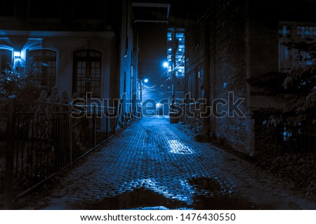Dark and scary vintage cobblestone brick city alley at night in Chicago Royalty-Free Stock Photo #1476430550