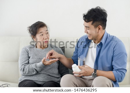 Asian man giving medicine to his mother, lifestyle concept. #1476436295