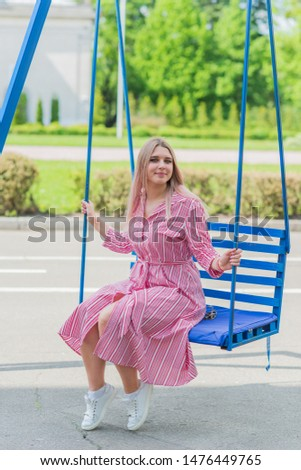 Cute simple woman with blonde hair of size plus size walks at park #1476449765