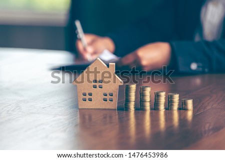 Modeling wooden houses and coins and dollars placed on wooden tables,preparation concept for house model purchase and the fastest growing real estate economy,moving home or renting property via agent Royalty-Free Stock Photo #1476453986
