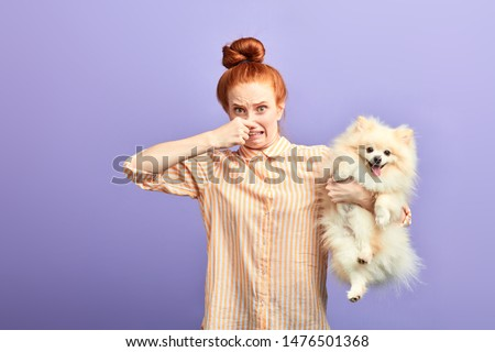 girl holding stinky stray dog, dirty pet needs to be washed, bad smell from dog's mouth. unpleasant smell from pet #1476501368