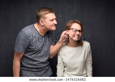Studio waist-up shot of dissatisfied man frowning face, pulling woman by ear while scolding, woman is grimacing from pain, over gray background. Strict boyfriend and misbehaving girlfriend #1476526682