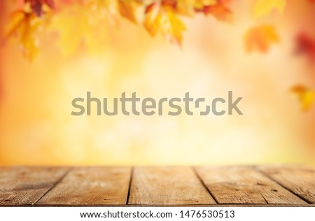 Wooden table and blurred Autumn background. Autumn concept with red-yellow leaves background. #1476530513