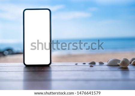 stock photo phone in the beach, black smartphone show white screen placed on wooden table with shells. Sky summer,beach and sea in background with copy space , blank for text ads and graphic design.