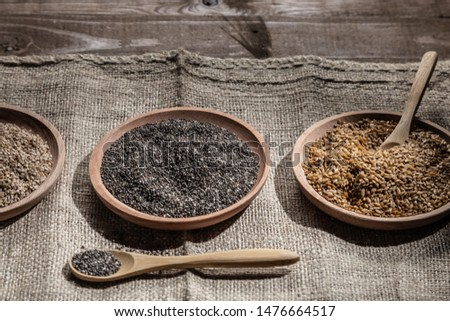 Sesame, chia and flax seeds in wooden dishes, wooden spoon with chia on wooden base.  #1476664517