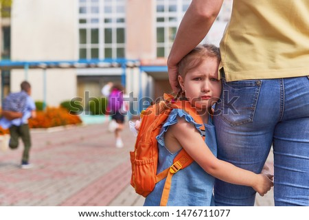 mother accompanies the child to school. mom supports and motivates the student. the little girl does not want to leave her mother. fears primary school. communication problems. attachment to parents. #1476711077